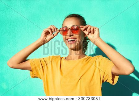 Fashionable Smiling Young Woman In Trendy Red Eyeglasses Posing On Blue Background, Wearing Yellow T