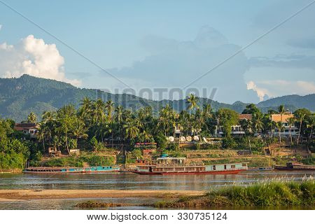 Traditional Long Boat On The Mekong River And Mountains View In Luang Prabang, Laos.