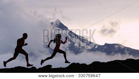 Running people athletes silhouette trail running in mountain summit background. Man and woman on run training outdoors active fit lifestyle.
