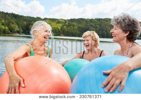 Three laughing senior women with gym ball have fun together