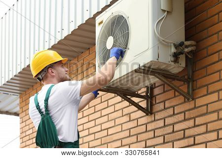 Professional Technician Repairing Modern Air Conditioner Outdoors