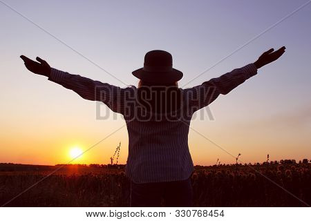 Blurred Silhouette Of A Woman Looking To The Sunset And Holding Hands Up. Cropped  Shot Of A Girl Ou
