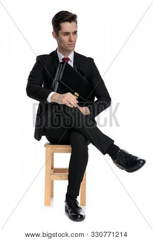 Bothered businessman holding his briefcase and looking away while wearing a black suit and red tie, sitting on a chair on white studio background