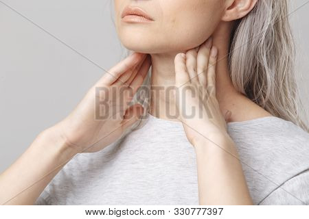 Female Checking Thyroid Gland By Herself. Close Up Of Woman In White T- Shirt Touching Neck With Red