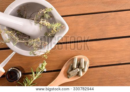 Homemade Elaboration Of Natural Medicines With Capsules And Mortar With Plants On Wooden Table. Alte