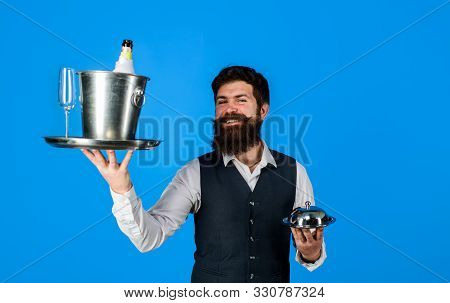 Butler. Professional Waiter In Uniform. Handsome Waiter With Serving Tray And Wine Cooler. Waiter. R
