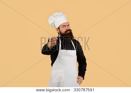 Cook In Uniform Pointing At You. Professional Chef Man In Cook Hat, Apron. Serious Chef With Beard,