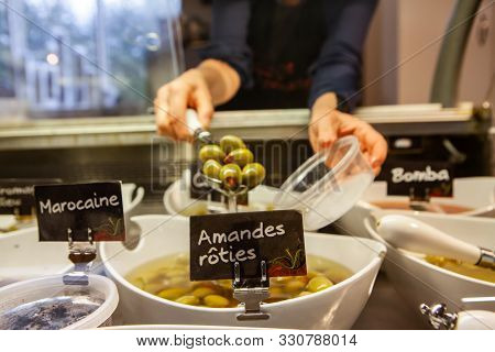 A Closeup View On The Hands Of A Shopper Filling A Tub With Fresh Green Olives From A Deli Food Coun