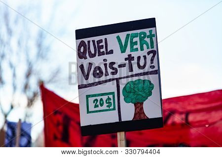 A Homemade French Sign, Saying What Green Do You See, Is Viewed Close-up, Held By An Environmentalis