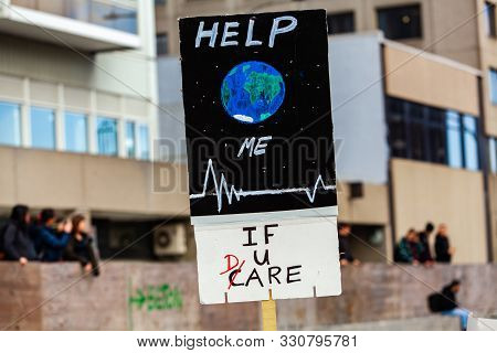 A Close Up View Of A Poster, Saying Help Me If You Care And Showing A Drawing Of Planet Earth As Env