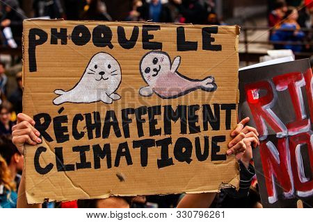 A Close-up View Of A French Placard Depicting Two Seals And The Words Seal Global Warming, As Enviro