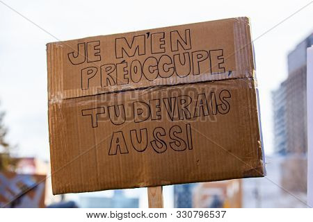 A Closeup View Of A Cardboard Sign Held By A French Protestor Saying I Do Care, You Should Too Durin