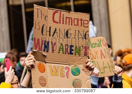 A Colorful Cardboard Placard Is Viewed Close Up, Saying The Climate Is Changing, Why Arent We, In Th