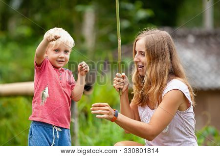 Happy Young Mother, Child Fishing Together With Fun. Little Funny Fisher Hold Caught Fish. Travel Li