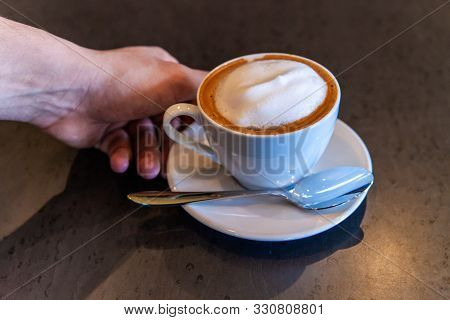 A Closeup View On A Persons Hand Reaching For A Freshly Prepared Latte In A Coffeeshop. Aromatic Bre