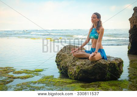 Young Woman Meditating, Practicing Yoga And Pranayama At The Beach. Hands In Gyan Mudra, Closed Eyes