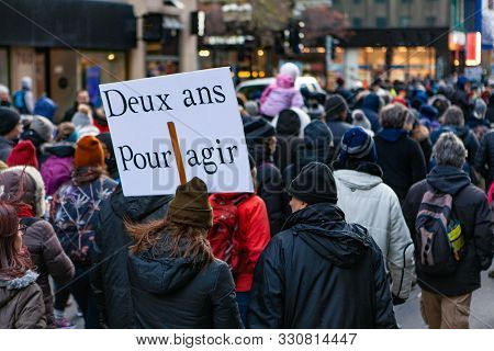 A French Sign Is Viewed Closeup, Saying Two Years To Act, Held By An Environmentalist Above A Large