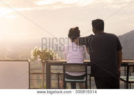 Asian Couples Are Watching The Beautiful Sunset On The Mountains At Petchabun Province , Thailand.