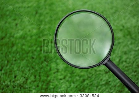 Easter theme: Loupe searching on grass
