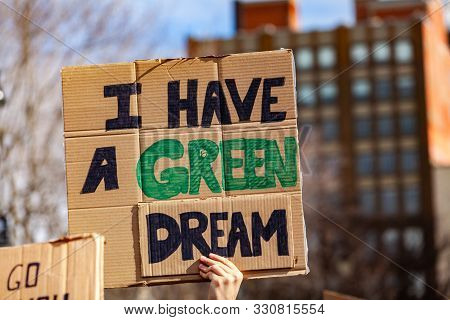 A Protestor Holds A Cardboard Sign, Reading I Have A Green Dream, Viewed Close-up As People Unite Ag