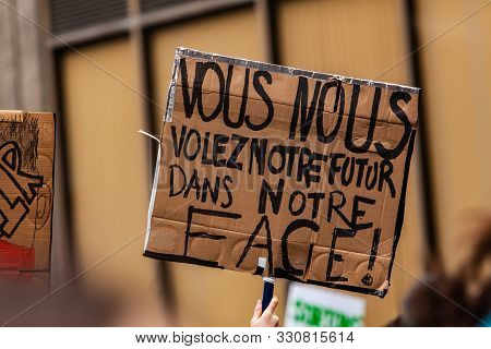 A Closeup View Of A Cardboard Sign With The French Words You Rob Us Of Our Future In Our Face, Being
