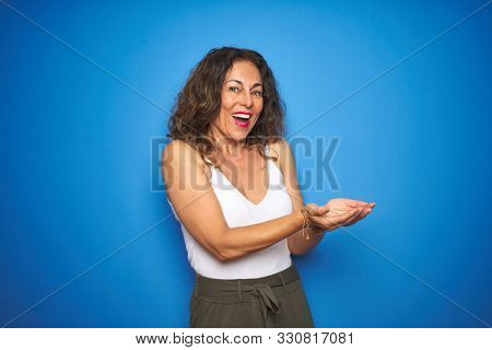 Middle age senior woman with curly hair standing over blue isolated background pointing aside with hands open palms showing copy space, presenting advertisement smiling excited happy