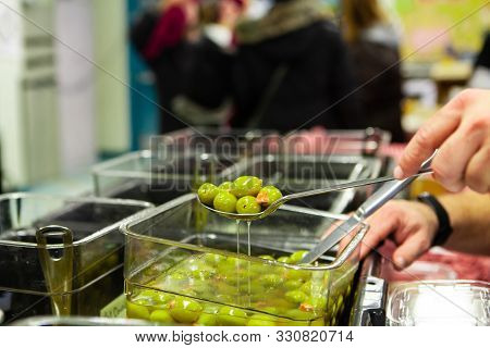 A Persons Hand Is Seen Up Close, Using A Large Serving Spoon To Scoop Green Olives From A Container