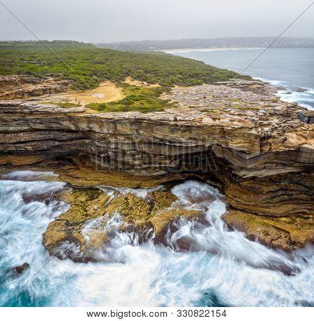 Coastal Erosion Of The Soft Sandstone Rocks Of A Sydney Headland On A Foggy Morning.