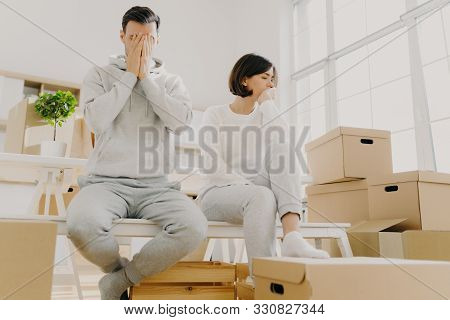 Worried Couple Pose Near Stack Of Cardboard Boxes, Have To Move In Other Flat, Have No Money For Ren