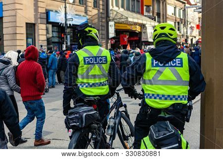 A Back View Of Police Officers On Bicycles Watching A Large Group Of People In A Town Center, Enviro