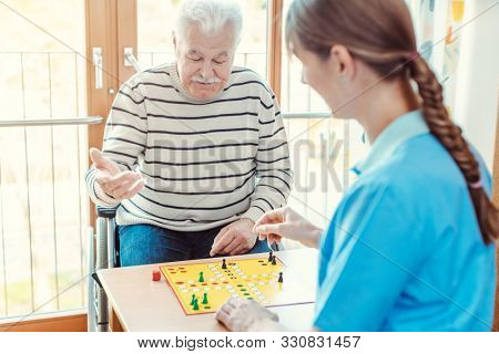 Nurse and senior in retirement home playing a board game together
