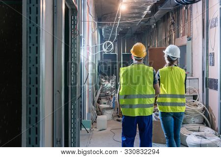 Builder and construction worker inspecting the site to plan further