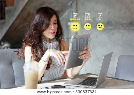 Beautiful Asian Woman In Casual Dress Pressing Smiling Face And Five Stars Emoticon On Tablet For Ev