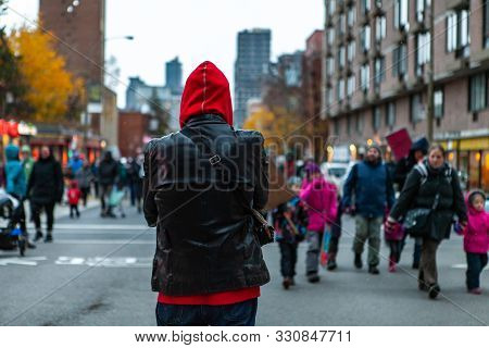 A Bystander Watches On As A Large Crowd Of Ecological Protestors Marches Towards The Camera, Person