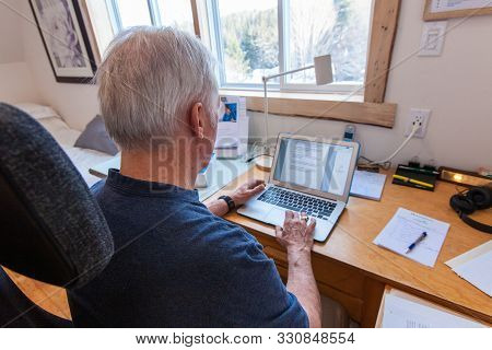 An Elderly Male Is Viewed From The Back, Sitting At A Light And Airy Workstation, Using A Laptop, No
