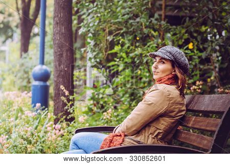 Beautiful Woman Smiling In Park. Happy People Lifestyle. Woman Smiling In Park While Sitting On Benc