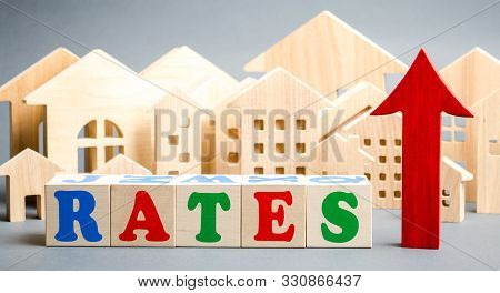 Wooden Blocks With The Word Rates, Up Arrow And Miniature Houses. The Concept Of High Interest Rates