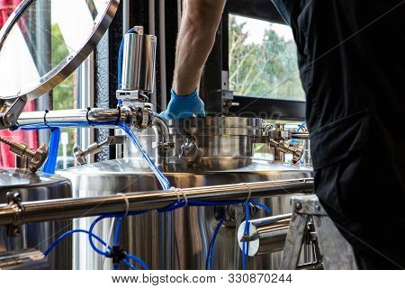An Employee Is Seen Closeup, Wearing Protective Gloves And Inspecting A Vat Of Fermenting Beer Insid