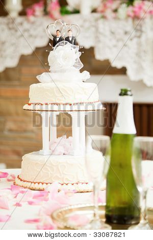 Wedding cake decorated with two grooms, on a reception table with champagne and rose petals.