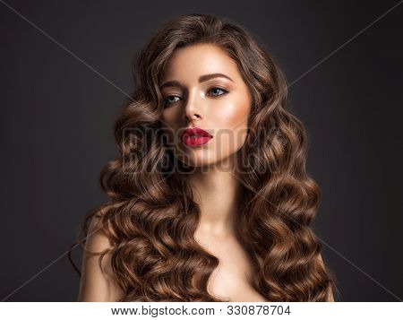 Beautiful woman with long brown hair. Beautiful face of an attractive model with red lipstick. Beauty  of curly hair. Closeup portrait  of caucasian stunning girl.