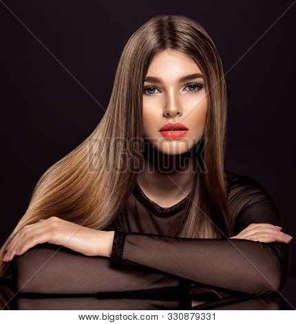 Woman with beauty long brown hair. Beautiful  model with long straight hair. Model with a smokey makeup. Pretty woman with orange color lipstick on lips.