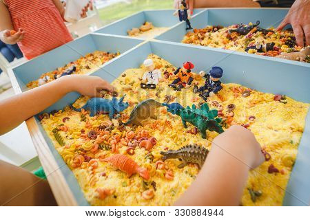 Child Plays With Toys Dinosaurs And Little Soldiers In An Artificial Yellow Sandbox. Little Green Di