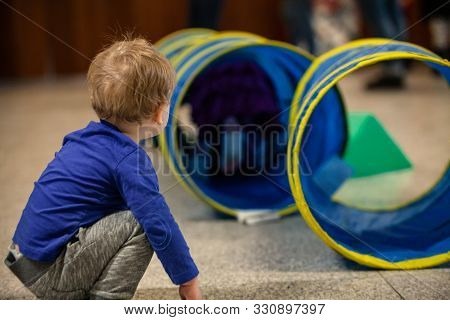 A Young Boy Is Viewed From The Side, Crouching Down To Look Through A Play Tent Tunnel During Playti