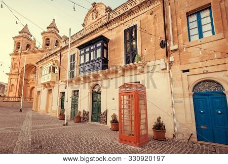 Marsaxlokk, Malta: Old Houses Street With Colorful Balconies And Retro Phone Booth On Mediterranean