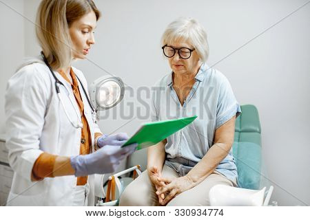Senior Woman Sitting On The Gynecological Chair During A Medical Consultation With Gynecologist. Con