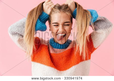 Portrait of a funny young blonde girl wearing sweater having fun isolated over pink background, pulling her hair out