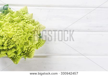 Fresh Green Romanesco, Raw Organic Cabbage Ready For Cooking On A Cutting Board On White Wooden Back