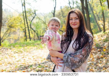 Lovely Mother And Child Walking In The Park. Mom With A Child In The Autumn On A Walk. Woman With Lo