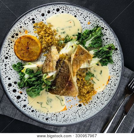 Spotted Wolffish Fillet With Spicy Bulgur And Fried Pak-choi And Lemon. Top View