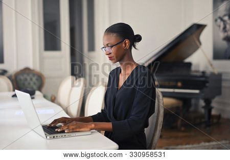 black woman work with laptop at home